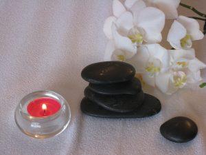 Fünf Steine und ein Teelicht vor einer Orchideenranke